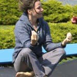 Cheryl sitting in meditation position bouncing on trampoline