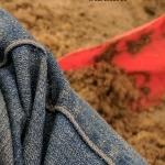closeup of jeans pant leg on sand