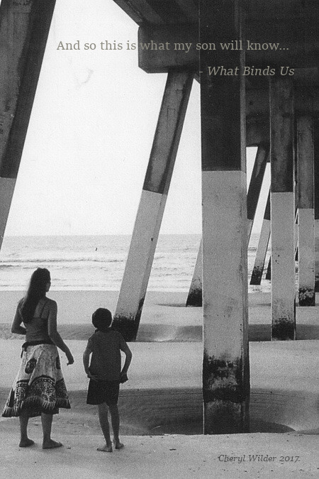 mother and young son stand underneath ocean pier