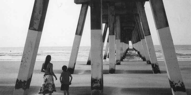 mother and young son standing underneath ocean pier