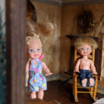 male doll sits in rocking chair with a female doll in doll house
